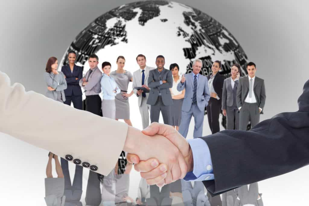Smiling business people shaking hands while looking at the camera against white earth with business terms